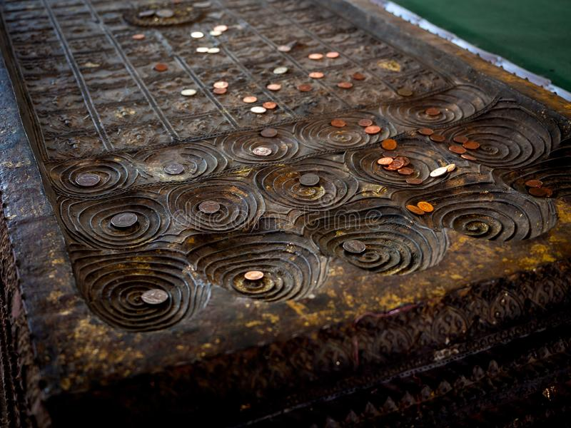 Many coins placed on replica of buddha footprint in the temple. Many coins, Thai baht placed on replica of buddha`s footprint in buddhist church in local temple stock photo