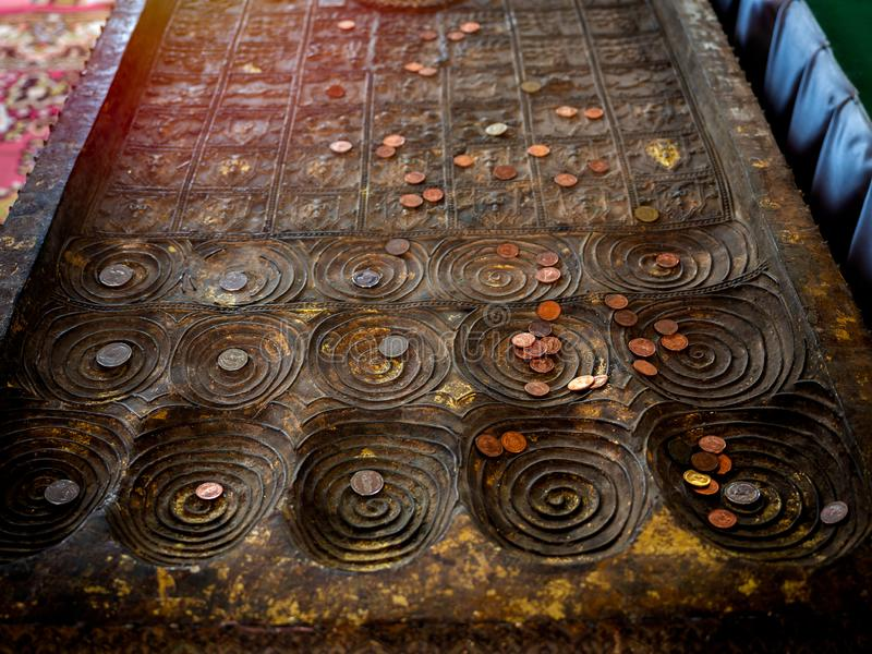 Many coins placed on replica of buddha footprint in the temple. Top view of many coins, Thai baht placed on replica of buddha`s footprint in buddhist church in royalty free stock images
