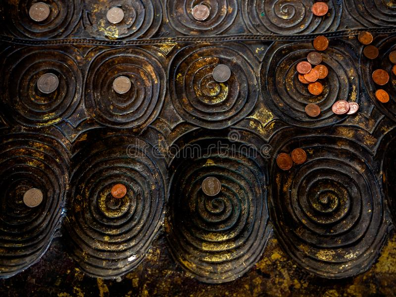 Many coins placed on replica of buddha footprint in the temple. Top view of many coins, Thai baht placed on replica of buddha`s footprint in buddhist church in stock photo