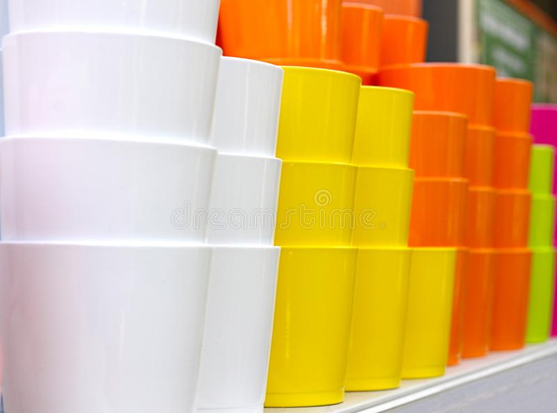 Many colored ceramic flower pots are stacked on a shelf in a garden equipment store. Yellow, white, orange, green and pink clay royalty free stock photos