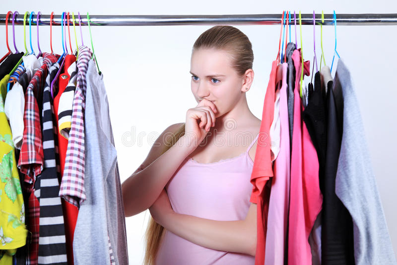 Many colored clothes on a hanger, girl questioned the choice of stock image