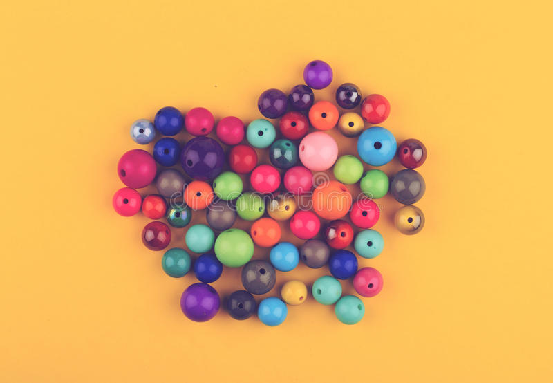 Many colored glass pearls beads on yellow background royalty free stock images