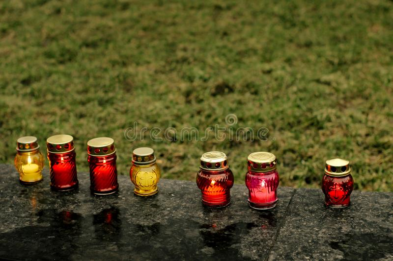 Many colorful candles with light burning in city center on marble stone, memorial day and sad bereavement moment stock images