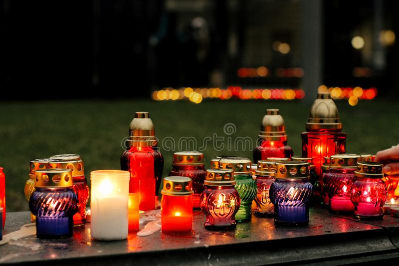 Many colorful candles with light burning in city center on marble stone, memorial day and sad bereavement moment royalty free stock images
