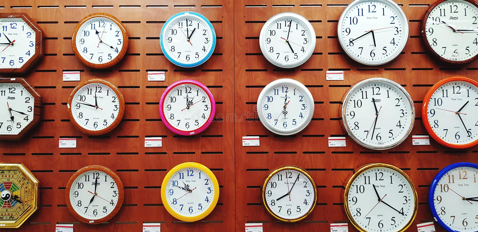 Many colorful group of clock hanging on brown wooden wall for sale at timing store. stock photography