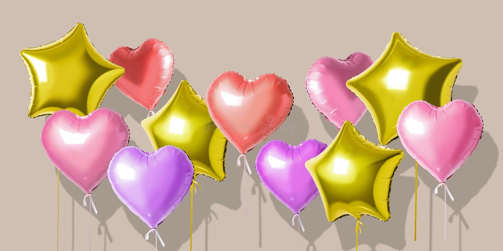Many colorful helium foil balloons of different shapes over bright background. Minimal holiday concept stock photo