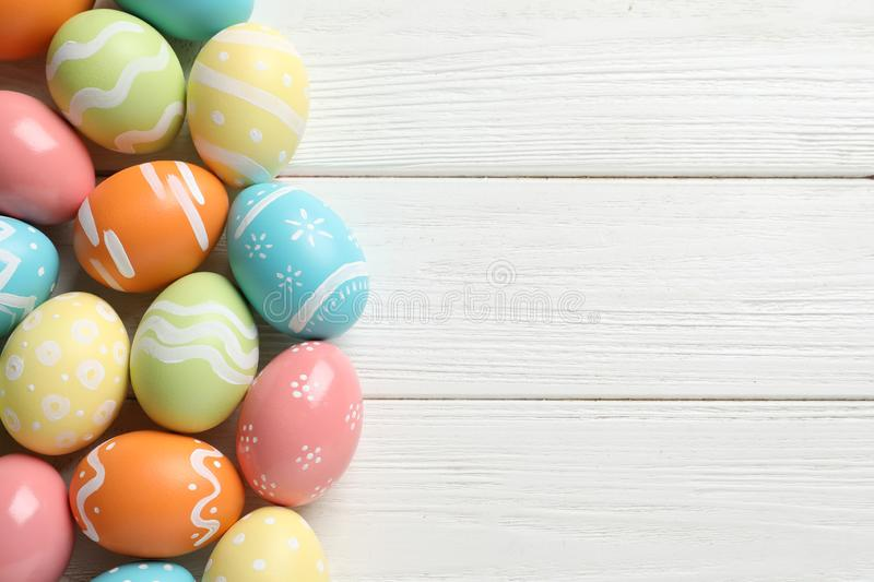 Many colorful painted Easter eggs on wooden background, top view. Space for text stock image