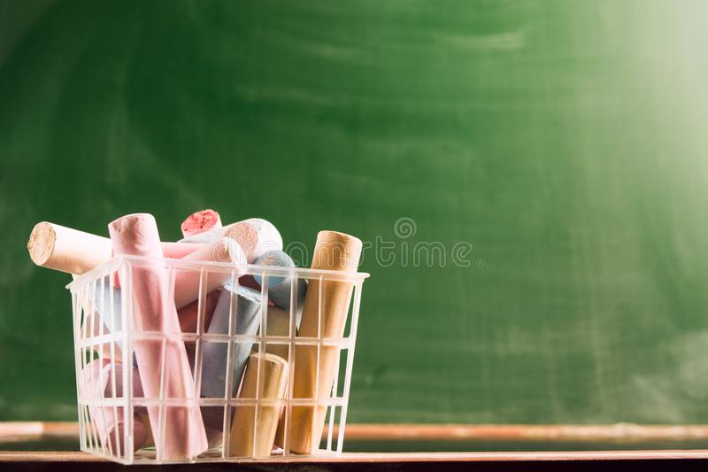 Many colorful piece of chalk in plastic basket. Back to school concept. Beginning school year. Closeup view with copy space. Selective focus stock photo