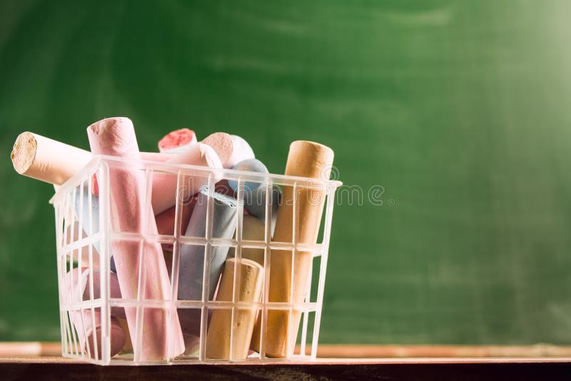 Many colorful piece of chalk in plastic basket. Back to school concept. Beginning school year. Closeup view with copy space. Selective focus stock photos