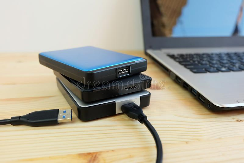 Many Colorful Portable external hard Drives USB3.0 connect to laptop computer on wooden. Background royalty free stock image