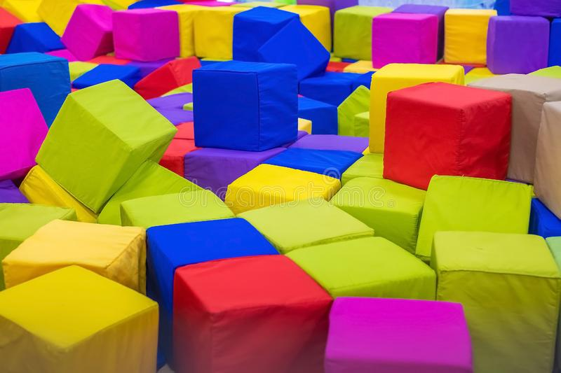Many colorful soft blocks in a kids` pool at a playground. Bright multi-colored soft cubes, geometric toys. Multicolored backgrou. Nd stock images