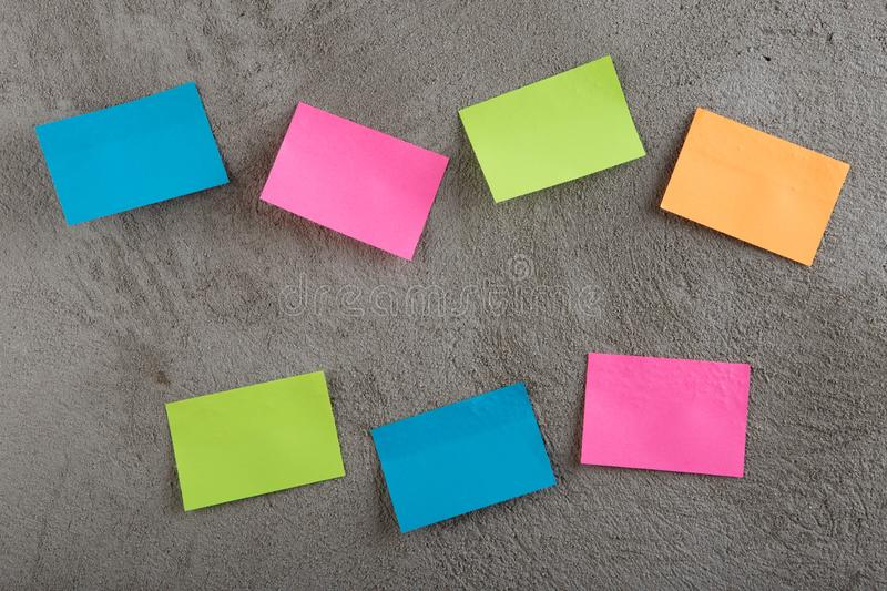 Many colorful sticky note on grey cement background. Copy space. Blank, empty, concrete, paper, reminder, sheet, sticker, announcement, board, bulletin stock images