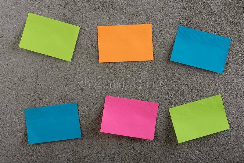 Many colorful sticky note on grey cement background. Copy space. Blank, empty, concrete, paper, reminder, sheet, sticker, announcement, board, bulletin stock photos