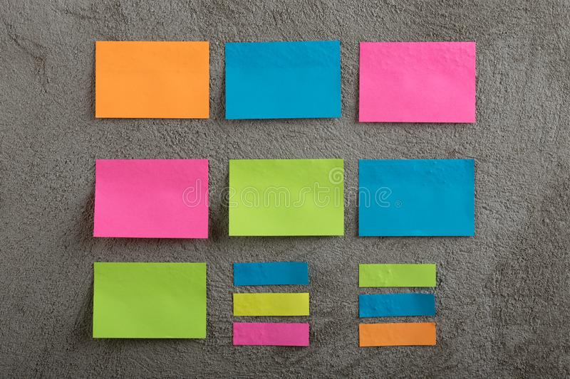 Many colorful sticky note on grey cement background. Copy space. Blank, empty, concrete, paper, reminder, sheet, sticker, announcement, board, bulletin royalty free stock photos