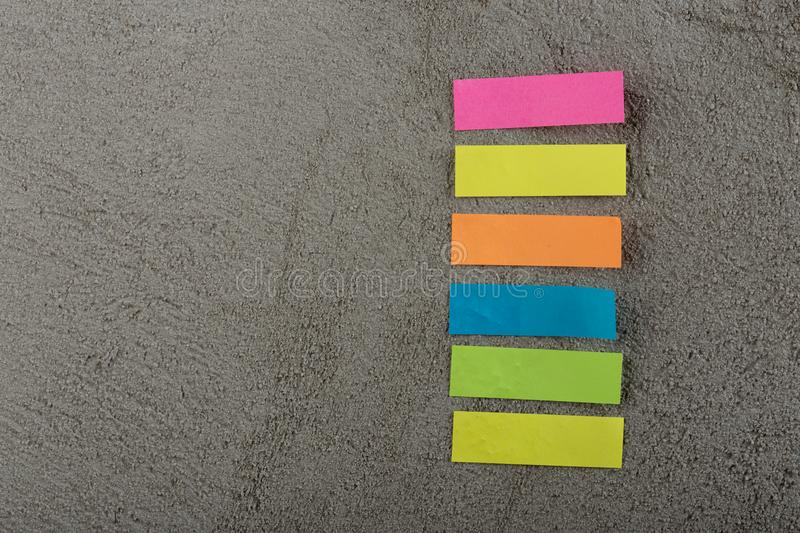 Many colorful sticky note on grey cement background. Copy space. Blank, empty, concrete, paper, reminder, sheet, sticker, announcement, board, bulletin stock image