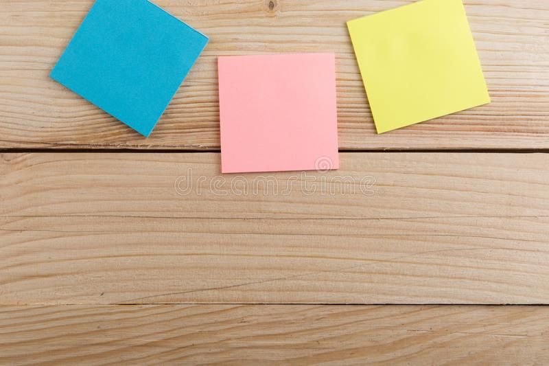 Many colorful sticky note on wooden desk. Copy space. Background, blank, empty, paper, reminder, sheet, sticker, announcement, board, bulletin, business, frame royalty free stock image