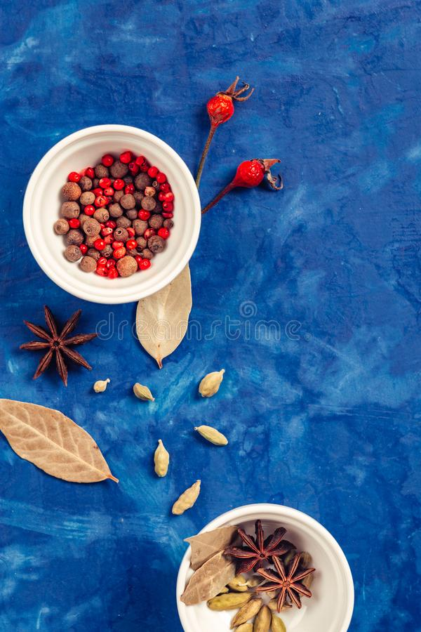 Many condiments. Spices different in small bowls on a blue background stock images