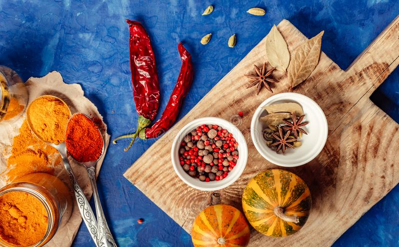Many condiments. Spices different in small bowls on a blue background stock photo