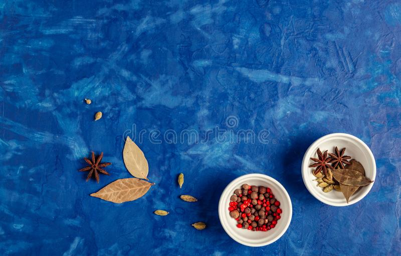 Many condiments. Spices different in small bowls on a blue background stock image