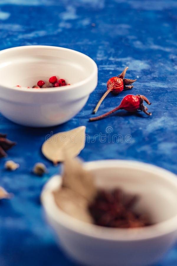 Many condiments. Spices different in small bowls on a blue background royalty free stock image