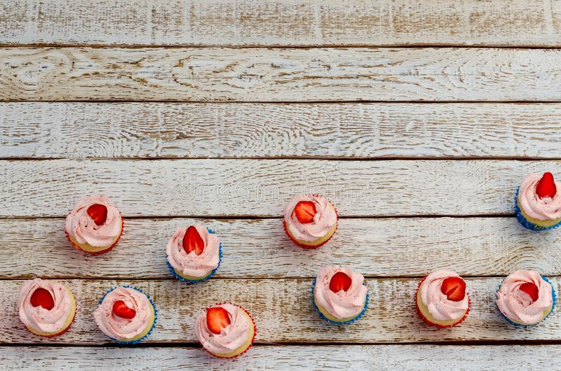 Many cupcakes on a wooden white table from above stock images