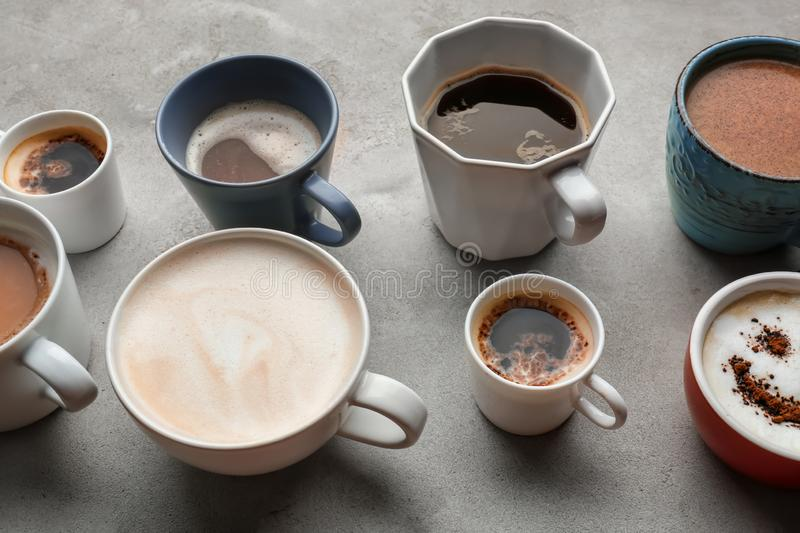 Many cups with tasty aromatic coffee on grey table royalty free stock images