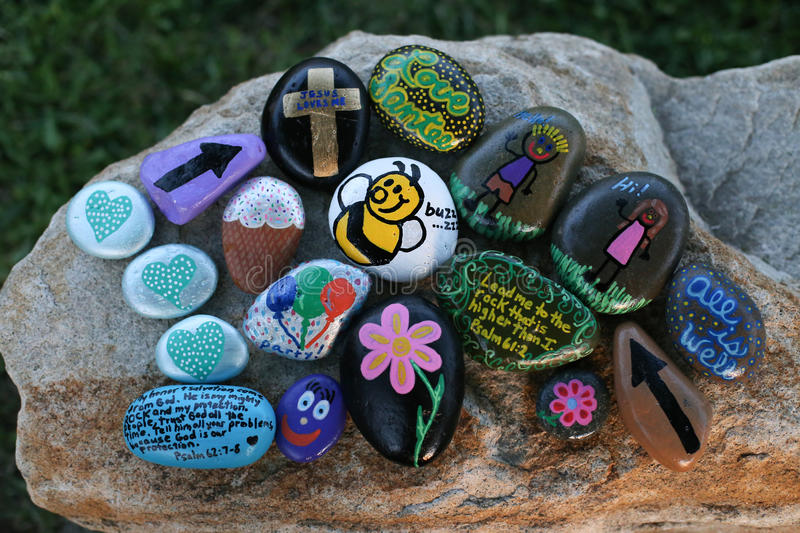 Many decorated painted rocks displayed on a small boulder stock image