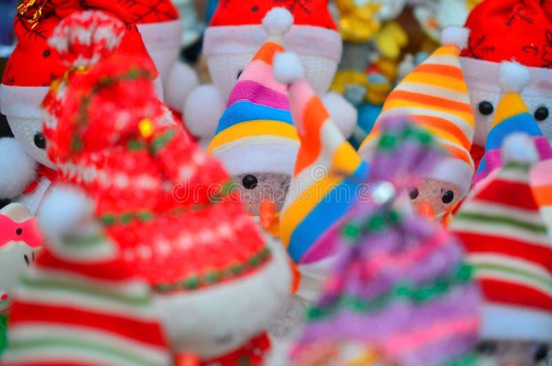Many decorative snowmen in bright hats at the Christmas market. stock photography
