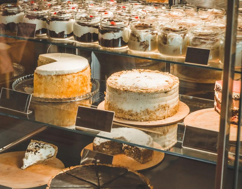 Many delicious cakes in the window of a cozy cafe. Tasty sweets. stock photography