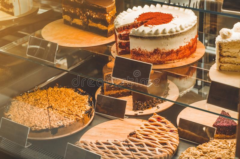 Many delicious cakes in the window of a cozy cafe. Tasty sweets. royalty free stock photography