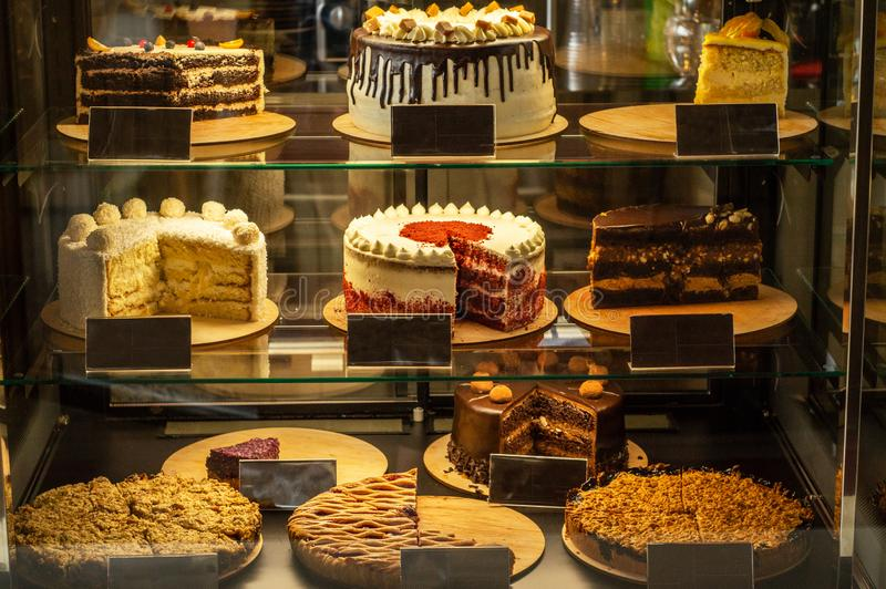 Many delicious cakes in the window of a cozy cafe. Tasty sweets. Many delicious cakes in the shop window of a cozy cafe. Tasty sweets royalty free stock image