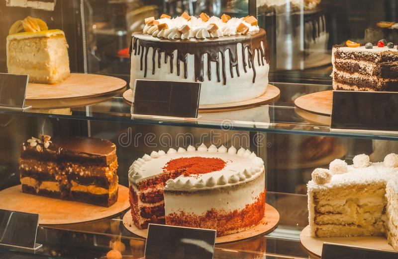 Many delicious cakes in the window of a cozy cafe. Tasty sweets. stock photo