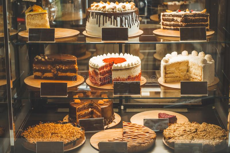 Many delicious cakes in the window of a cozy cafe. Tasty sweets. stock images