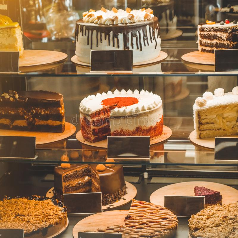 Many delicious cakes in the window of a cozy cafe. Tasty sweets. Many delicious cakes in the shop window of a cozy cafe. Tasty sweets stock photography