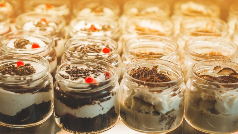 Many delicious desserts in a jar on the window of a cozy cafe. Tasty sweets.  royalty free stock photos