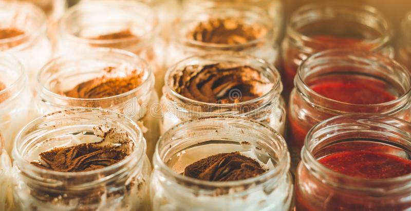Many delicious desserts in a jar on the window of a cozy cafe. Tasty sweets stock images