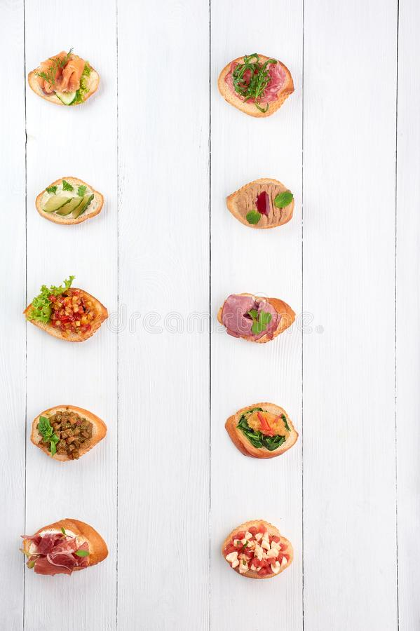 Many different bruschettas at white wooden table top royalty free stock photos