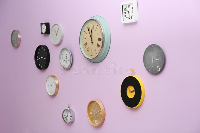 Many different clocks hanging on color wall royalty free stock photos