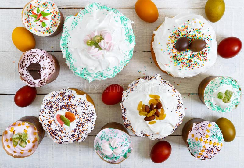 Many different Easter cakes and colorful painted eggs on a white wooden background. Top view. Traditional sweet bread decorated meringue and sweets stock photo