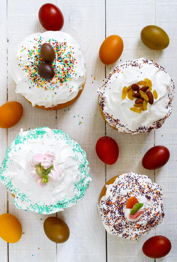 Many different Easter cakes and colorful painted eggs on a white wooden background. Traditional sweet bread decorated. Many different Easter cakes and colorful stock photos