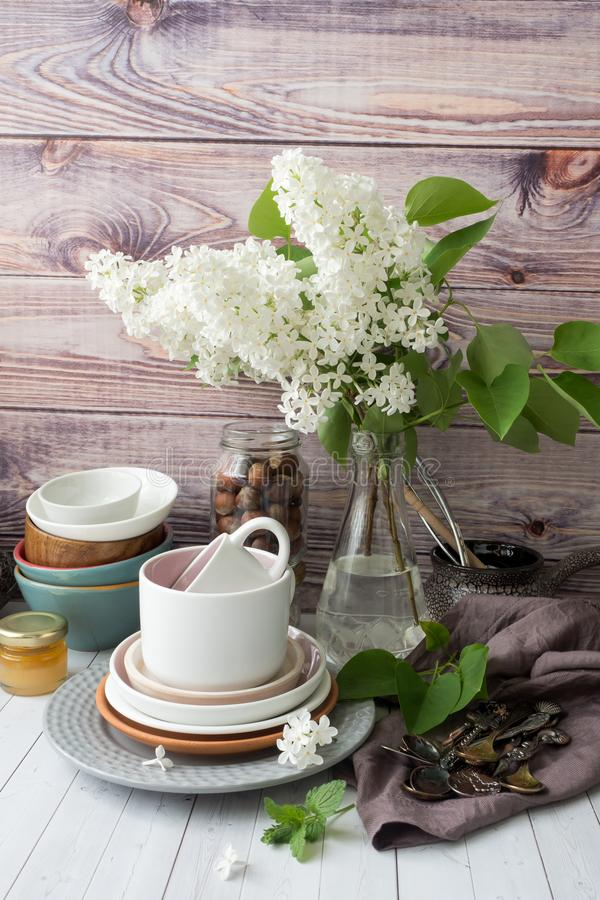 Many different empty tableware. Bouquet of white lilac. Wood background dark napkin stock images