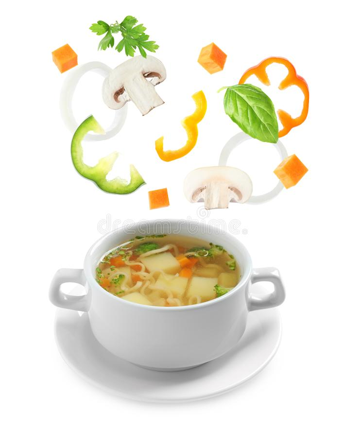 Many different ingredients falling into bowl of homemade vegetable soup stock image