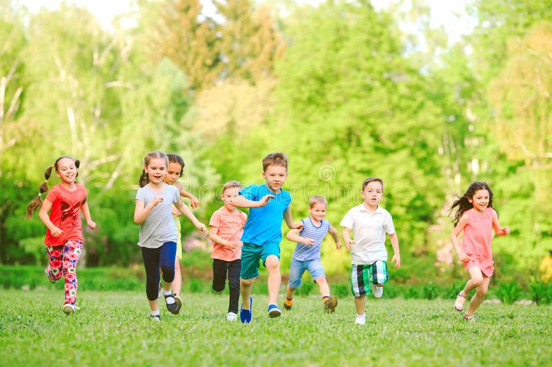 Many different kids, boys and girls running in the park on sunny summer day in casual clothes stock images