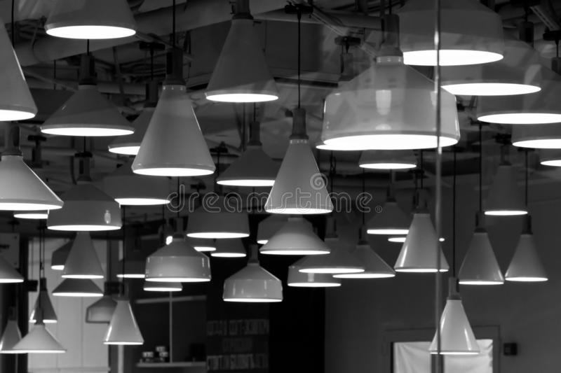Many different lamps are hanging from above. Black and white. royalty free stock image