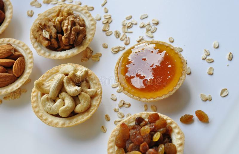 Many different nuts poured into tartlets with honey royalty free stock images