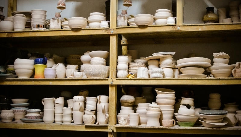 Many different pottery standing on the shelves in a workshop royalty free stock photography