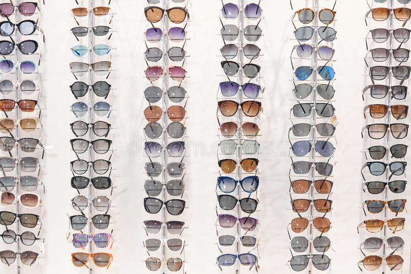 Many different sunglasses on display shelves in store royalty free stock photo