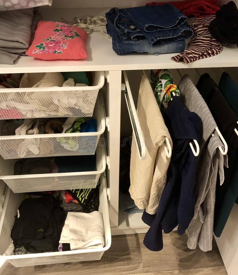 Many different things hang and lie in the closet in the wardrobe. Many different things hang and lie in the closet in the wardrobe stock photos