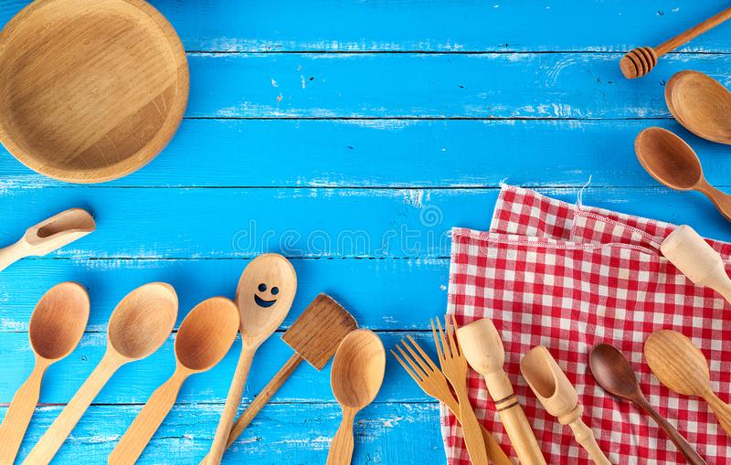 Many different wooden spoons, forks and empty plate on a blue background. Copy space, kitchen backdrop royalty free stock photos