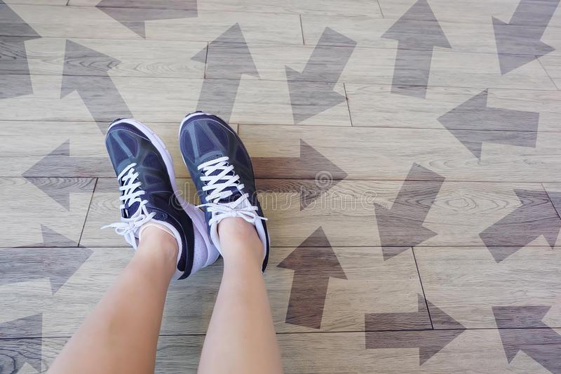 Many Direction Arrow Choices. Selfie of Running Shoes with Drawn Arrows. Woman Violet Sneakers with Decisions on Wooden Floor Back. Ground Great For Any Use royalty free stock images
